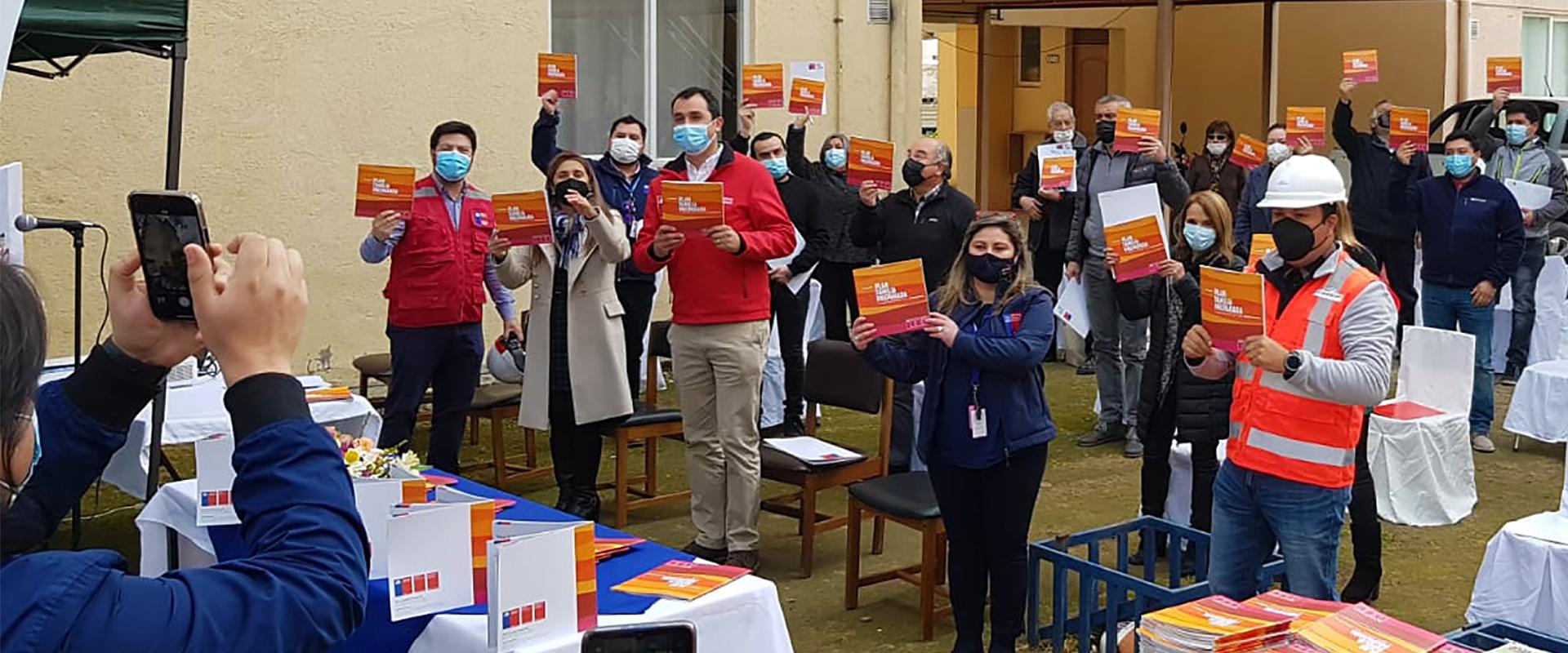 familias del condominio abate molina y autoridades muestran el folleto del Plan Familia Preparada